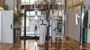 dos hombres desinfectando el hotel, como serán restaurantes y hoteles después del coronavirus