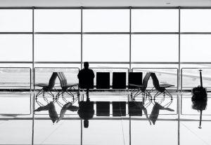 un hombre sentado esperando en el aeropuerto - roam vibes