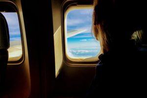una chica sentada en el avión mirando por la ventana